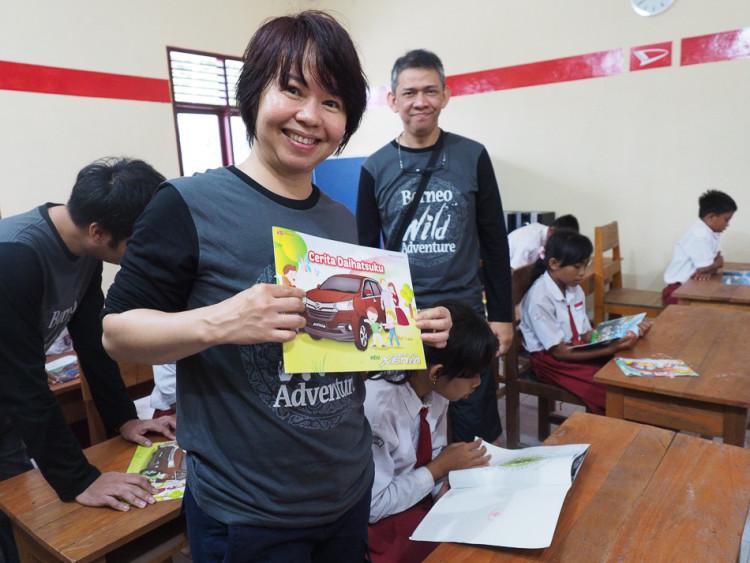Ibu Amel dari daihatsu sedang membagikan buku untuk anak-anak.